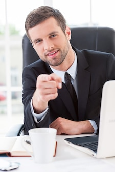 Делаем бизнес проще. уверенный молодой человек в строгой одежде, указывая на вас и улыбаясь, сидя на своем рабочем месте