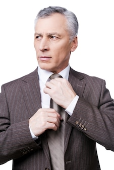 Making business look good. confident mature man in formalwear adjusting his necktie and looking away while standing against white background