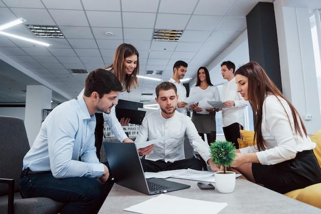 사업 계획 만들기. 사무실에서 젊은 프리랜서 그룹 대화 및 미소
