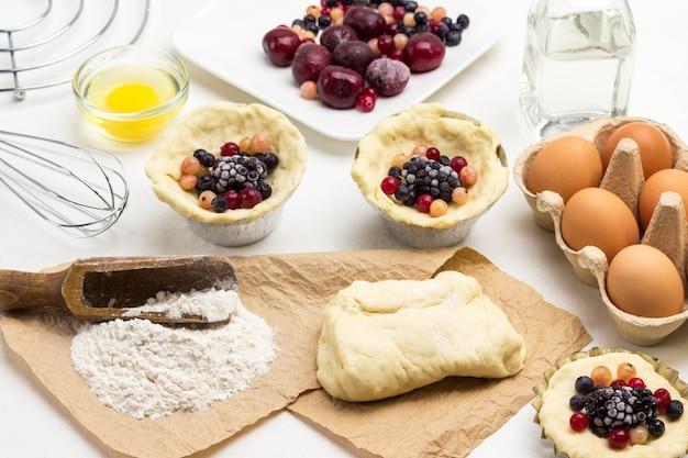Делаем торт из замороженных ягод. бумага, мука, тесто. тесто и ягоды в чашке для выпечки. белый фон. вид сверху