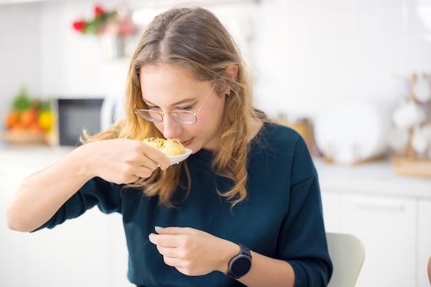 Делать торты и печенье - это очень весело. на кухне молодая женщина держит вкусный свежий хлеб.