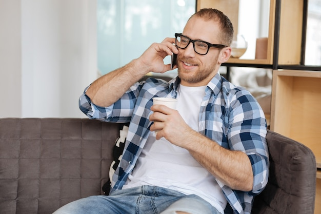 Making a call. handsome positive delighted man having coffee and using his cell phone while sitting comfortably on the sofa