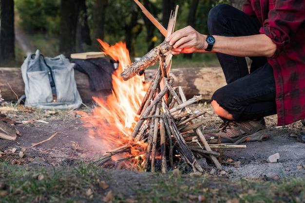 森でキャンプファイヤーを作る。ワイルドなコンセプトを取り入れます。ヴィンテージのバックパック、魔法瓶、カジュアルな服装の男性がいるキャンプ場では、木片を燃やします。