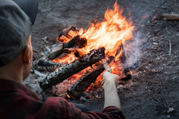 森でキャンプファイヤーを作る。カジュアルな服装の男性が木片を燃える火に入れます。