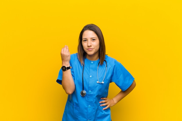 Making capice or money gesture, telling you to pay your debts! isolated against yellow wall