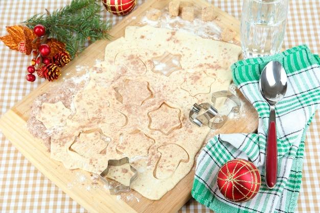 식탁보 배경의 나무 판자에 크리스마스 쿠키 만들기