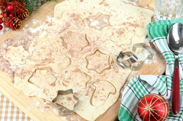 Изготовление рождественского печенья на деревянной доске на поверхности скатерти