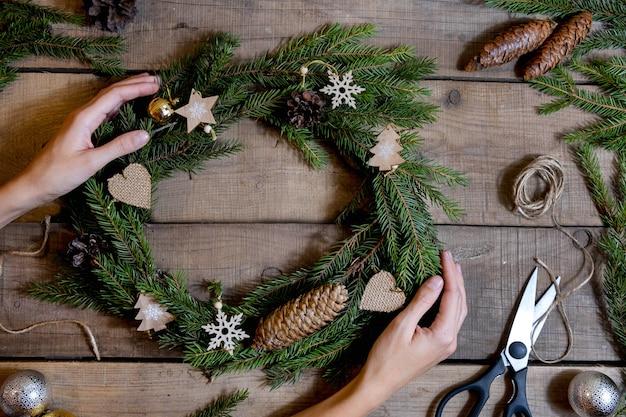 Делаем рождественский эко венок. еловые ветки, шишки, ножницы, джутовая веревка, деревянные украшения. детали для мастерской изготовления рождественского венка
