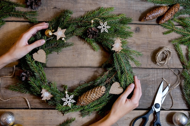 Making christmas eco wreath. fir branches, cones, scissors, jute rope, wooden decorations. details for workshop of making christmas wreath