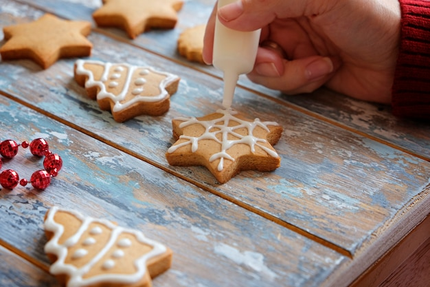 Making christmas ginger cookies with white glaze decoration
