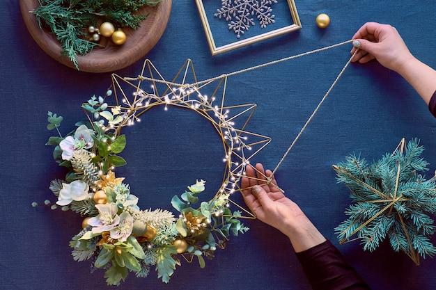 Изготовление рождественского венка, креативная плоская планировка, вид сверху женскими руками, венок ручной работы на металлической основе, рождественские украшения и натуральные растения.