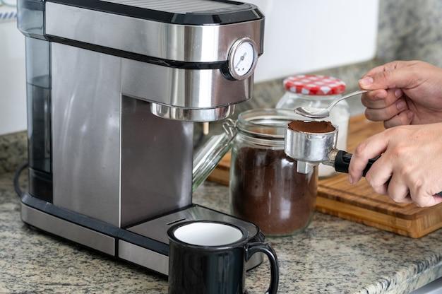フィルターでコーヒーを押すエスプレッソマシンで自宅でコーヒーを作る。