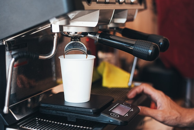 Making coffee in a disposable cup with a coffee machine