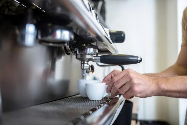 Приготовление кофе. мужские руки кладут две белые чашки в кофемашину в помещении, лица не видно
