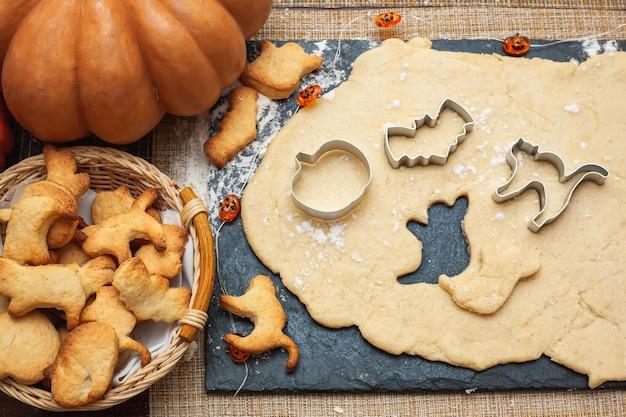 ハロウィン用のクッキー作り。カボチャ、猫、幽霊、コウモリの形で生地からクッキーを切り取ります。