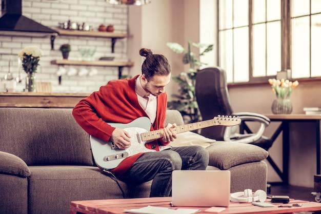 表紙を作る。ノートパソコンで音楽を聴き、カバーを作る黒髪の才能のあるミュージシャン