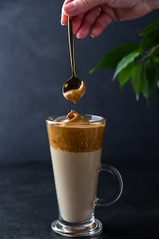 Приготовление далгона кофе. рука с ложкой взбитой пены