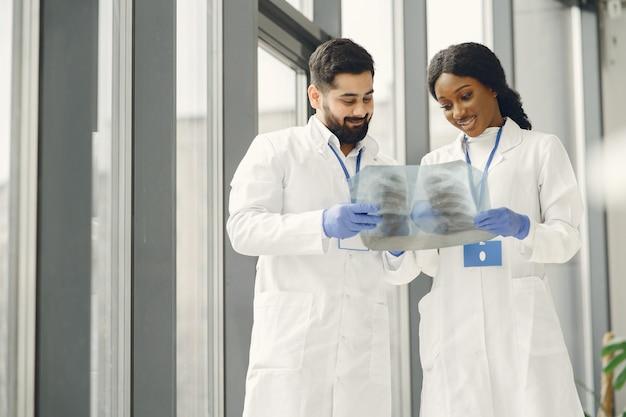 診断をチームのタスクにする。患者のレントゲンを見る医師。