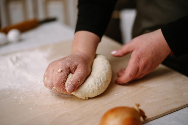 빵집에서 여성 손으로 반죽 만들기. 요리, 요리, 빵집 개념.