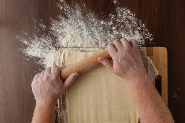 Making dough by mens hands on wooden table