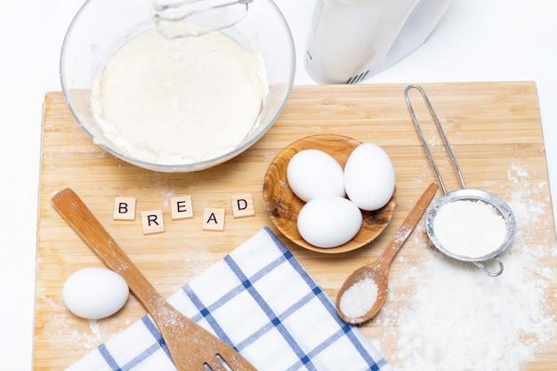 パンや自家製焼き菓子の生地を作る。木製のテーブルの食材。碑文:パン