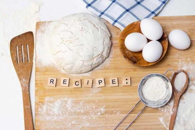 Делаем тесто для хлеба или домашней выпечки. ингредиенты на деревянном столе. надпись: рецепт