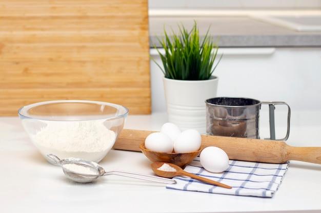 パンや自家製焼き菓子の生地を作る。テーブルの上の材料。明るくモダンなキッチンを背景に