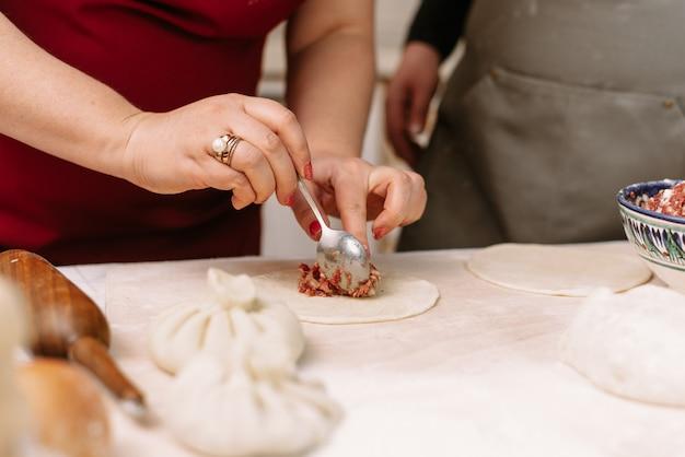 Приготовление пельменей, манты и хинкали из рубленой говядины, баранины и теста. домашняя еда