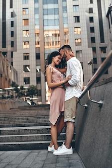 서로를 행복하게 만드는 것. 야외에 서 있는 동안 껴안고 웃고 있는 아름다운 젊은 부부의 전체 길이