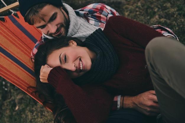 서로를 행복하게 만드는 것. 야외에서 해먹에 누워 있는 동안 껴안고 웃고 있는 아름다운 젊은 부부의 상위 뷰