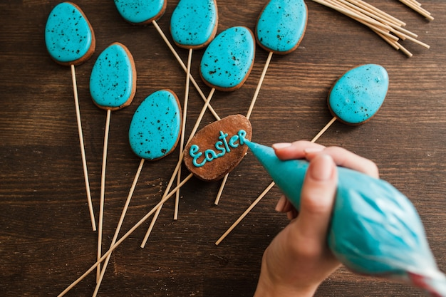 Making easter blue cake pops on wooden rustic table