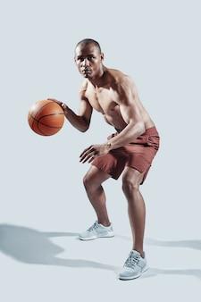 努力する。灰色の背景に対してバスケットボールをしながらカメラを見てスポーツ服を着たハンサムな若いアフリカ人の全長