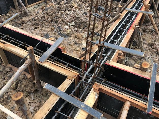 Изготовление фундамента из стали и дерева для цементных полов под зданием.
