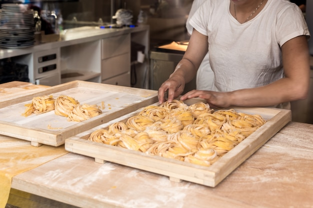 Making fresh homemade italian pasta tagliatelle in restaurant