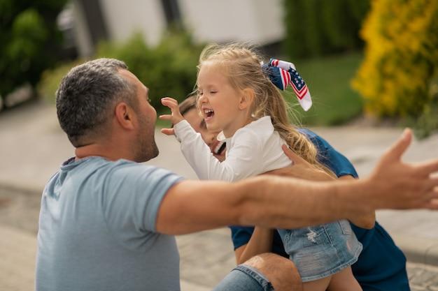 Гримасничаю. милая блондинка делает смешное лицо, обнимая родителей, стоящих на улице