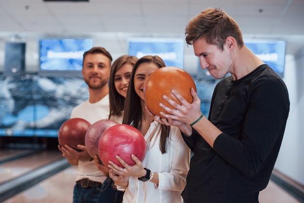 Fare una faccia buffa. i giovani amici allegri si divertono al bowling durante i fine settimana