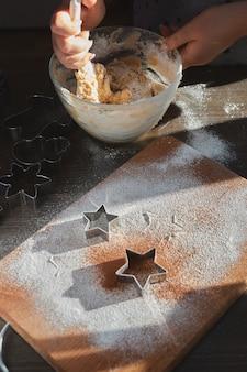 ジンジャークッキー生地を作る。若い女性の手がガラス板に混ざり合ってジンジャーブレッドマンの生地を焼きます。家でのごちそう、家族の夕食のコンセプト。