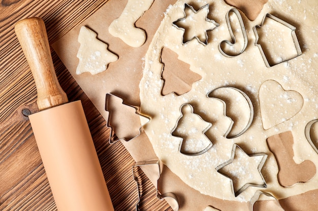 Making gingerbread christmas cookies using form for cooking on wooden background