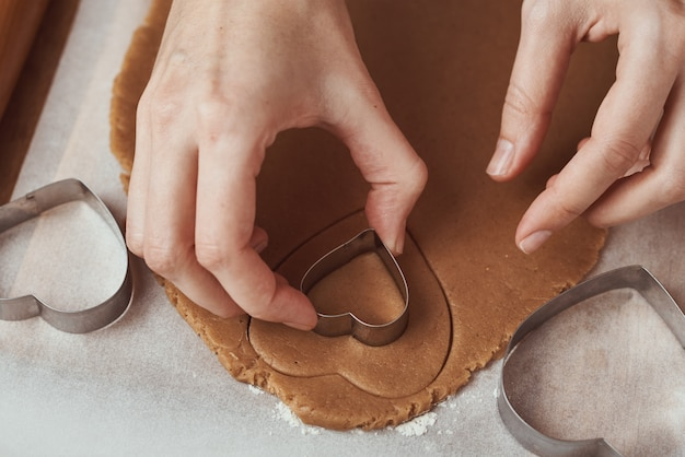 Making gingerbread cookies in shape of a heart for valentines day. woman hand use cookie cutter. holiday food concept