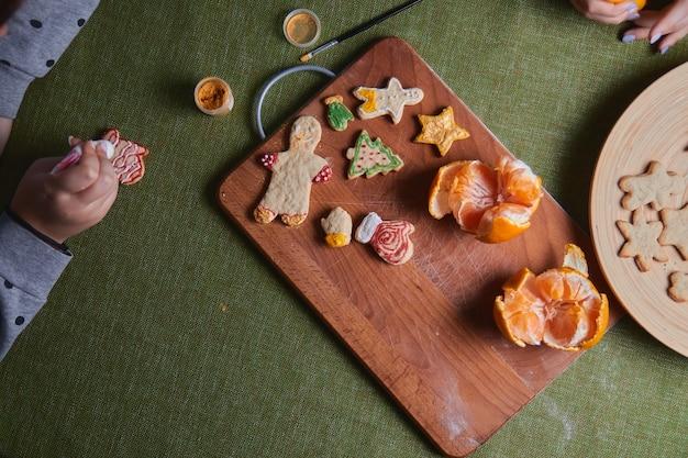 Делаем пряничный человечек, тесто для печенья. концепция застолья в доме, семейного обеда. концепция новогодних традиций и процесс приготовления. печенье на деревянном зеленом столе.