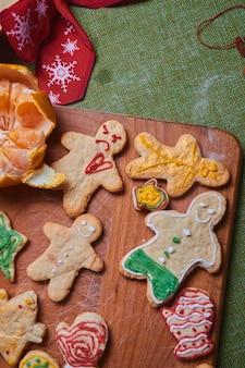 ジンジャーブレッドマン、クッキー生地を作る。家でのごちそう、家族の夕食のコンセプト。新年の伝統のコンセプトと調理プロセス。木製の緑のテーブルの上のクッキー。