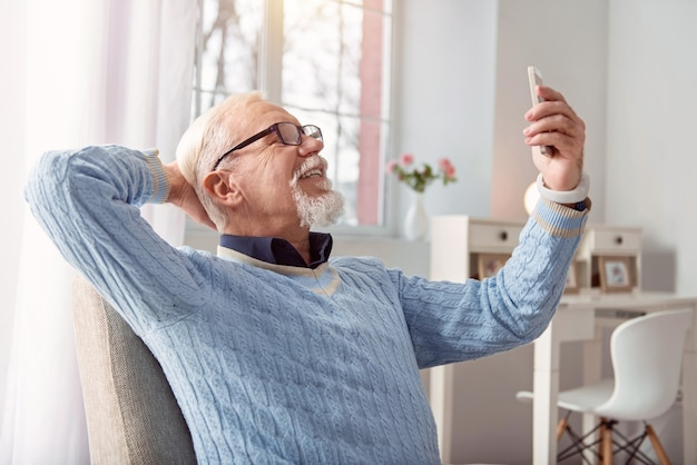Making good memory. pleasant upbeat senior man sitting in the armchair and posing, smiling widely, while taking selfies