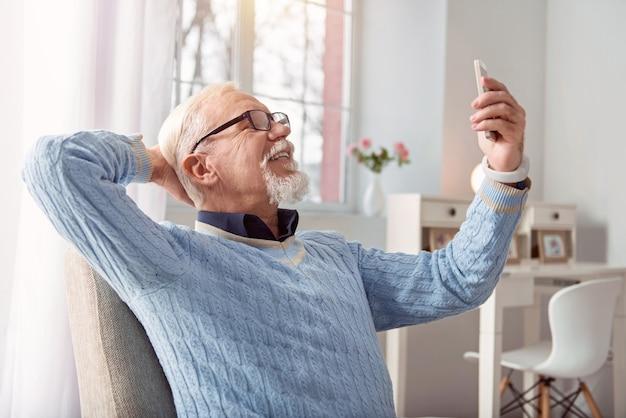 良い思い出を作る。肘掛け椅子に座ってポーズをとって、セルフィーを撮りながら広く笑っている楽しい明るいシニア男性