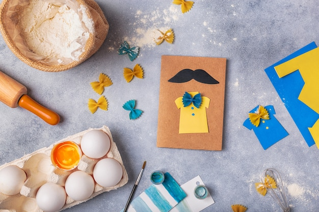Making greeting card for fathers day. shirt with butterfly from pasta. card from paper. moustache. childrens art project.