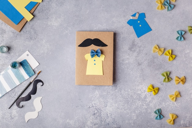 Making greeting card for fathers day. shirt with butterfly from pasta. card from paper. moustache