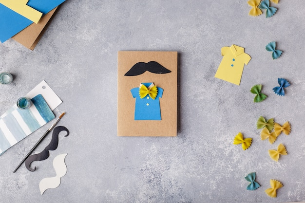 Making greeting card for fathers day. shirt with butterfly from pasta. ]childrens art project.