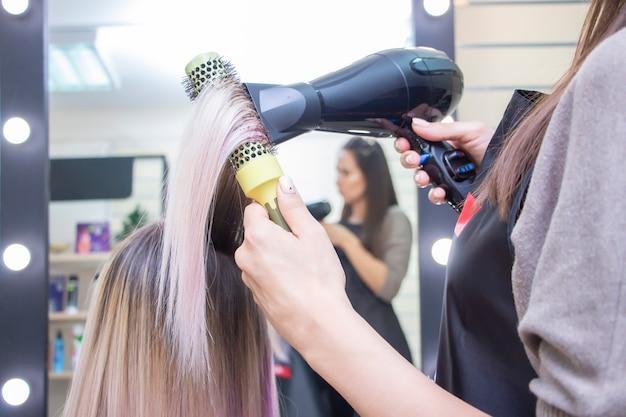 ドライヤーで髪型を作る。サロンで長いブロンドの髪を持つ少女。理髪店。