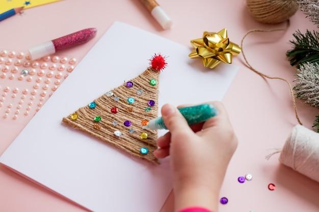手作りのクリスマスカードを作る。子供のdiyコンセプト。クリスマスのおもちゃの装飾やグリーティングカードを作る