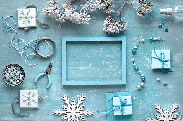 Making handmade jewelry for friends as christmas gifts. flat lay on mint textured background.