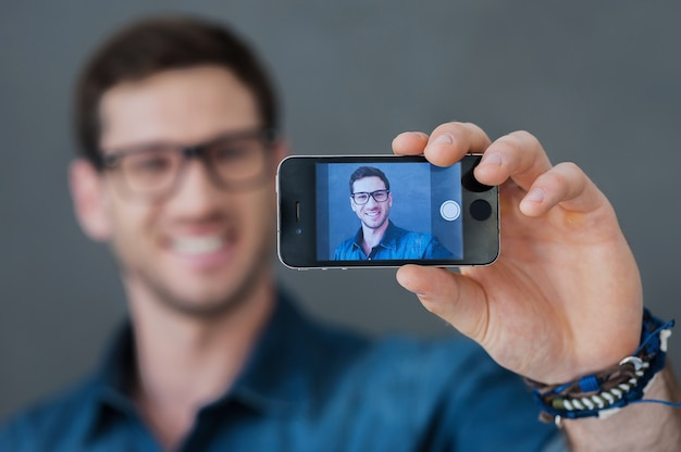 Making happy selfie. smiling young man making selfie by his smart phone